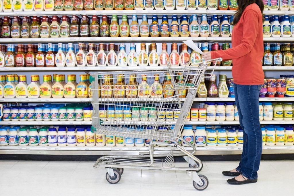Shopper checking list in supermarket aisle