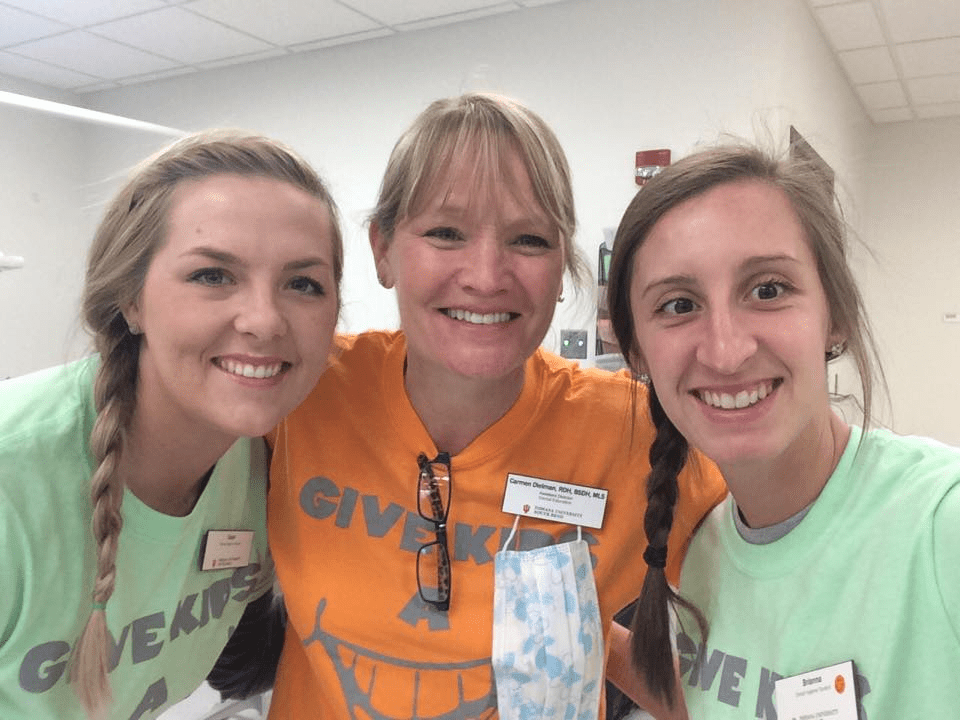 Dr. Carmen Dielman with two former students (Cayla Swihart and Brianna Hensley) at the Give Kids a Smile Day at IUSB