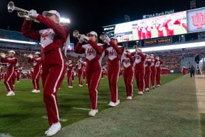 Trumpet players lined up on the field.