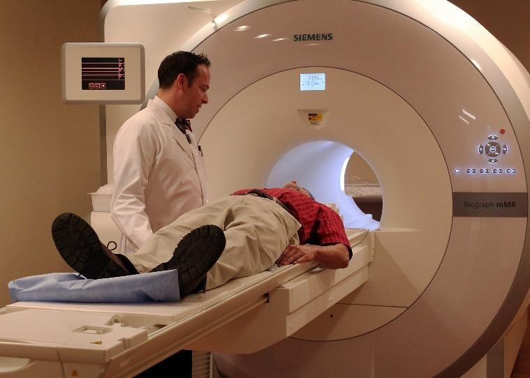 A doctor inserts a patient into a large cylindrical MRI scanner.