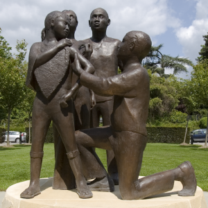 A statue depicting a child receiving a vaccination shot in the upper arm from a kneeling person.