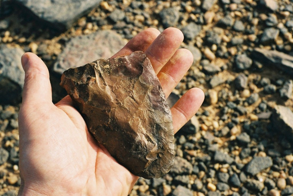 A hand holding a triangular stone tool, which was made millions of years ago.