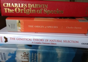 a stack of biology books, including On the Origin of Species