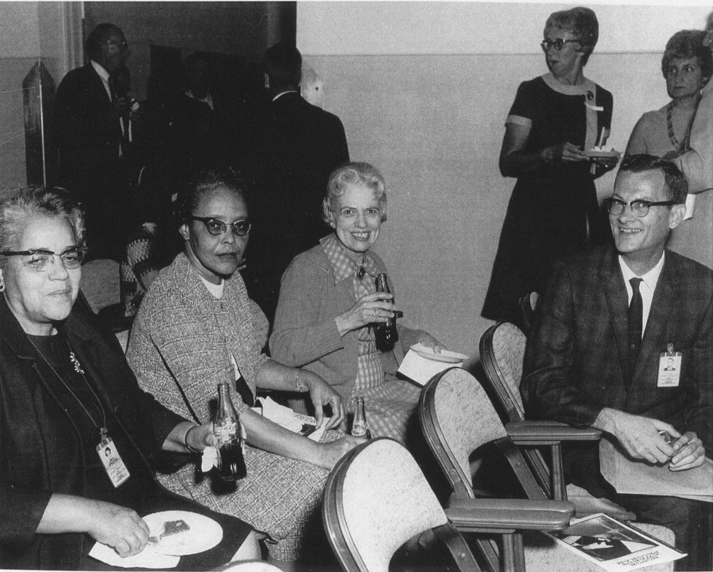 An original black and white photograph of Dorothy Vaughn sitting with two other women and one man. All are dressed in business clothing and wear badges, likely those required while working at NASA. Each is drinking a glass bottle of soda and smiling. Two other women and three men stand in the background, talking to one another.