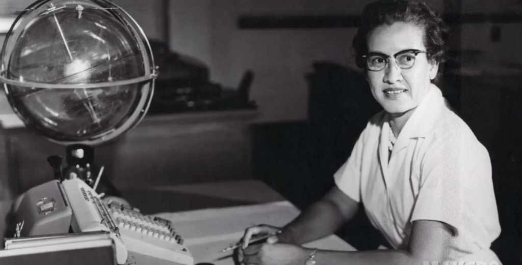 An original black and white photograph of Katherine Johnson. She is sitting at a desk, holding a pencil, and smiling. On the desk there is a notepad, pencil, large calculator, and statue of a globe.