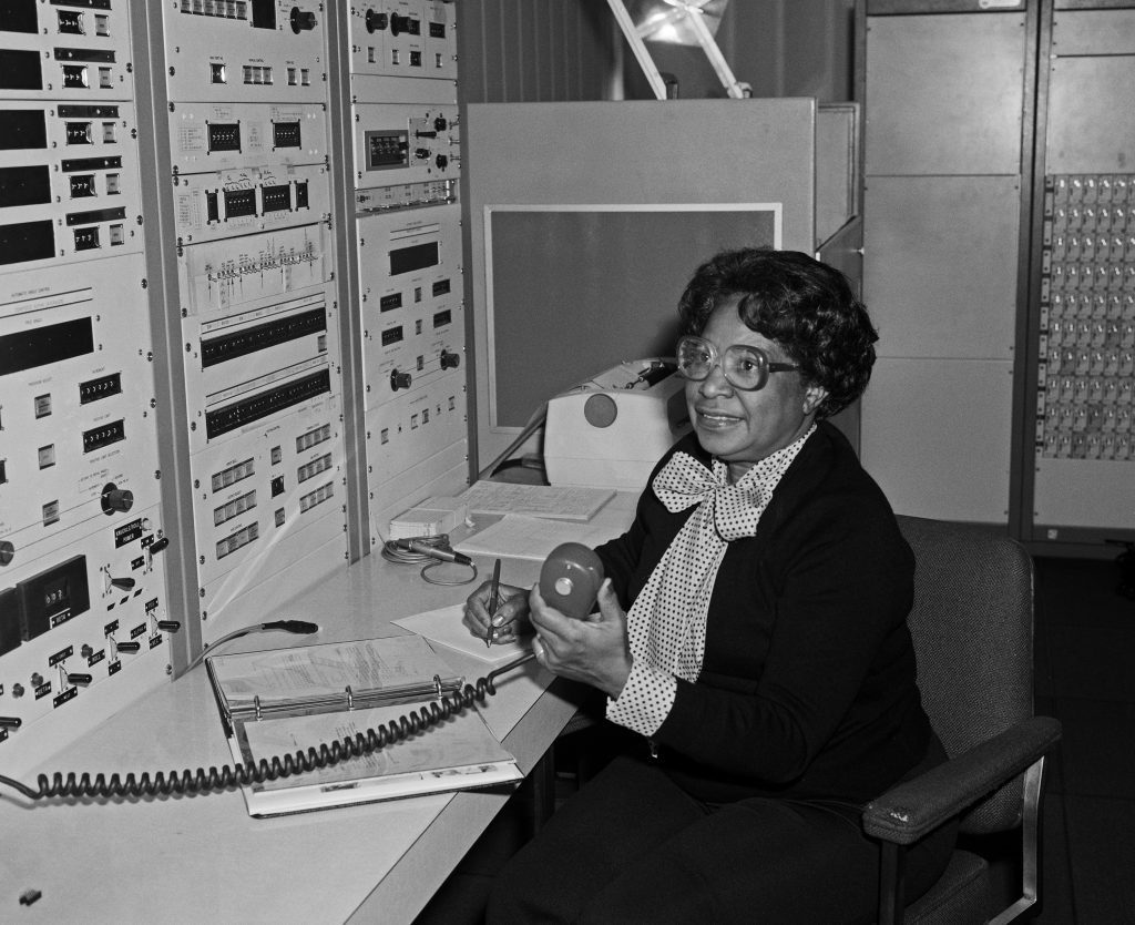 An original black and white photograph of Mary Jackson. She is sitting at a desk, holding a pencil and an intercom microphone, and smiling. On the desk are a notepad and binder. In front of her, lining the wall shown on the left side of the photograph, is what appears to be a large computer. Its surface is covered with knobs, switches, and sockets.