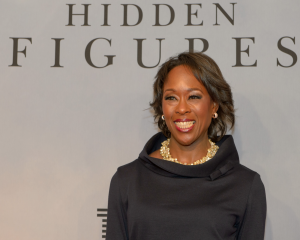 "A photograph of Margot Lee Shetterly, who is elegantly dressed and standing in front of a backdrop that reads, ""Hidden Figures""."