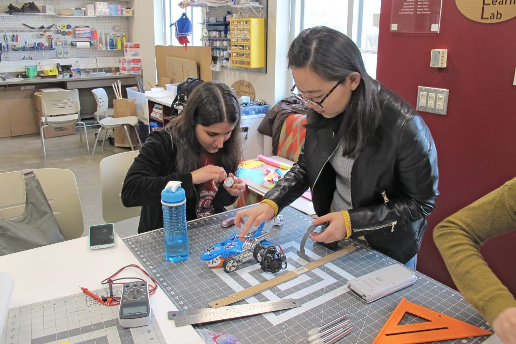 Two graduate students are at a table in the MILL working on building a small robot