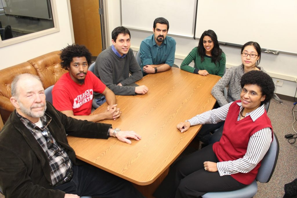 A group photograph of seven members of the Mathematical Psychology Lab, sitting around a conference table.