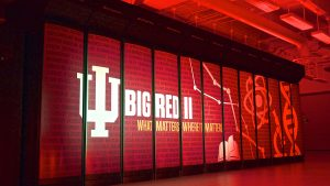 """A photo of a side of a supercomputer, on the illuminated red panels are the words """"Big Red II"""" along with Indiana University's symbol and the words """"What Matters Where It Matters"""""""