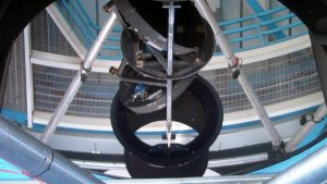 A curved mirror takes up the entire image, reflecting the interior roof of the building that houses the telescope and the casing that holds the additional mirror.
