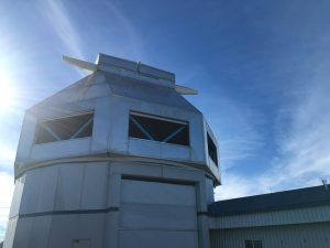 Looking up at a large silver building, vaguely octagonal in shape, that contains the WIYN telescope. There is a blue sky behind it.