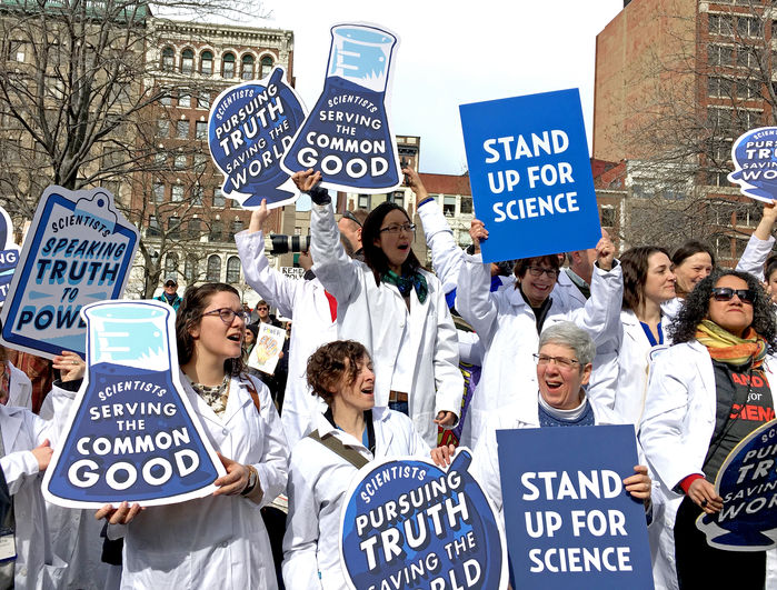 "Science activists wearing white lab coats hold signs such as ""Scientists serving the common good,"" ""Stand up for science,"" and ""Scientists speaking truth to power."" They are gathered at a rally in Boston to ""Stand Up for Science."" Many of the rally participants were also attendees at the AAAS annual conference during the same afternoon."