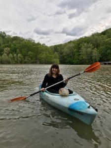 A women sits in a blue boat (kayak) holding a double-sided paddle in the middle of a lake. Trees and cloudy background.