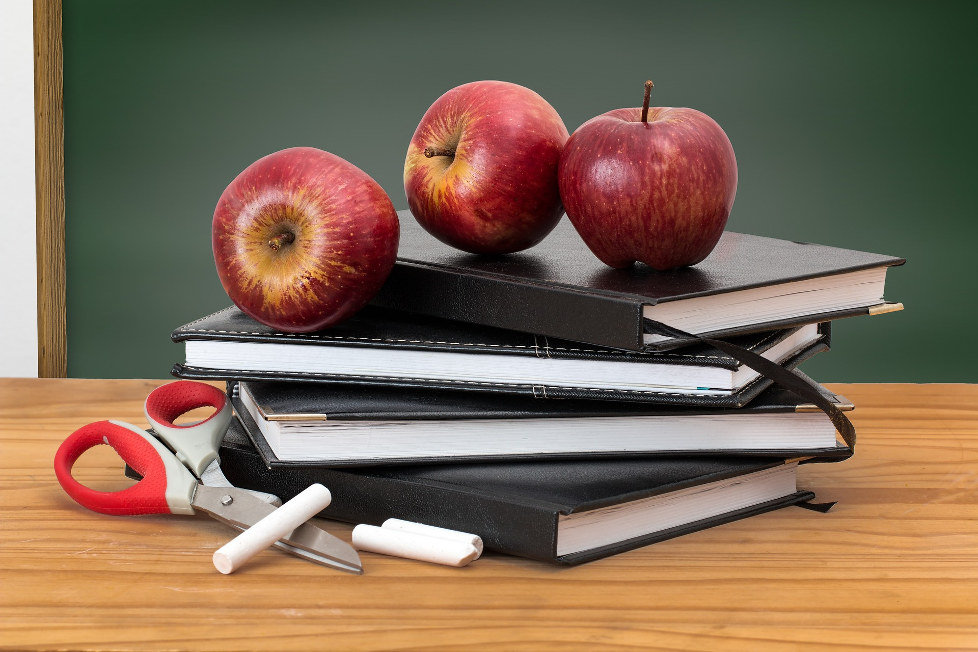 A stack of books lay on a desk in front of a blackboard. On top of the books are three apples. Next to the books are a pair of scissors and many pieces of chalk.