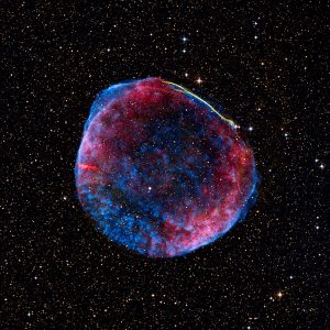 Against a backdrop of stars, a semi-transparent sphere of blue and red dust explodes outward from a central point. A thin line of yellow outlines a small section.
