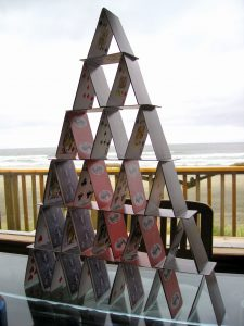 Pairs of cards leaning against each other form triangles that stack on top of other pairs to form a pyramid of cards with six layers.