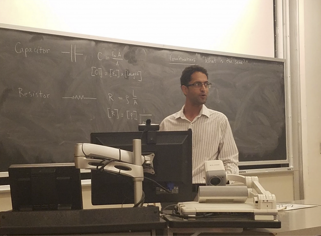 A man stands in front of a chalkboard, where equations are written. There is also a computer on a desk in front of him.