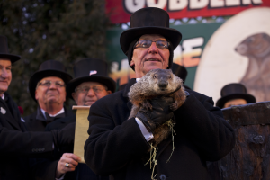 A man in a top hat holds a small groundhog, Punxsutawney Phil, with other Groundhog day spectators in the background.