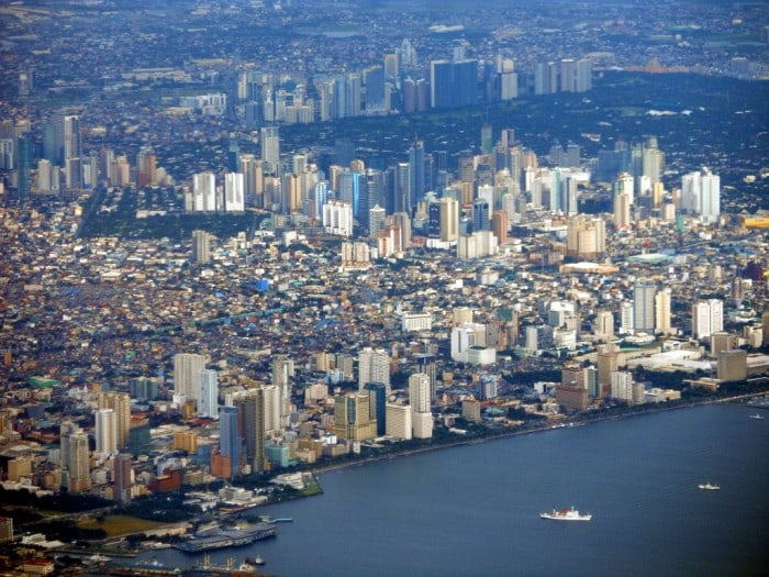 An image of the city of Manila, in the Philippines, from the sky. The image shows many skyscrapers located close together, next to the ocean.
