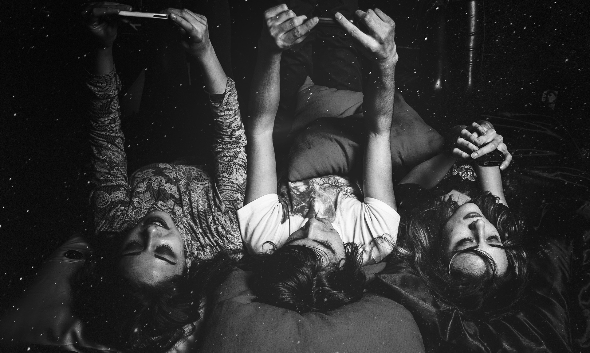 In a black and white photo, three people, two women and one man, are lying in bed facing up with their arms holding their phones above their heads.