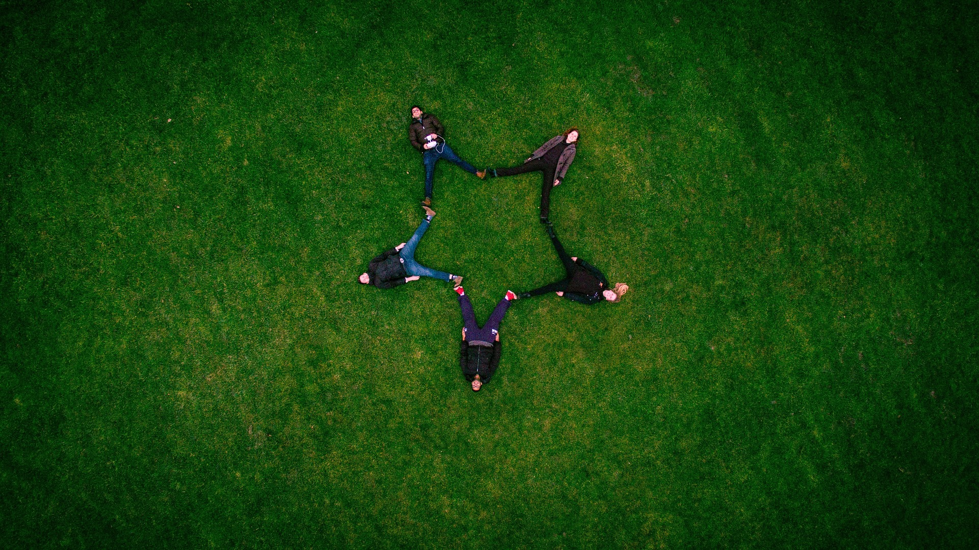 Atop a large green field, five people are lying on the grass such that their legs are meeting on each side to form the shape of a star.