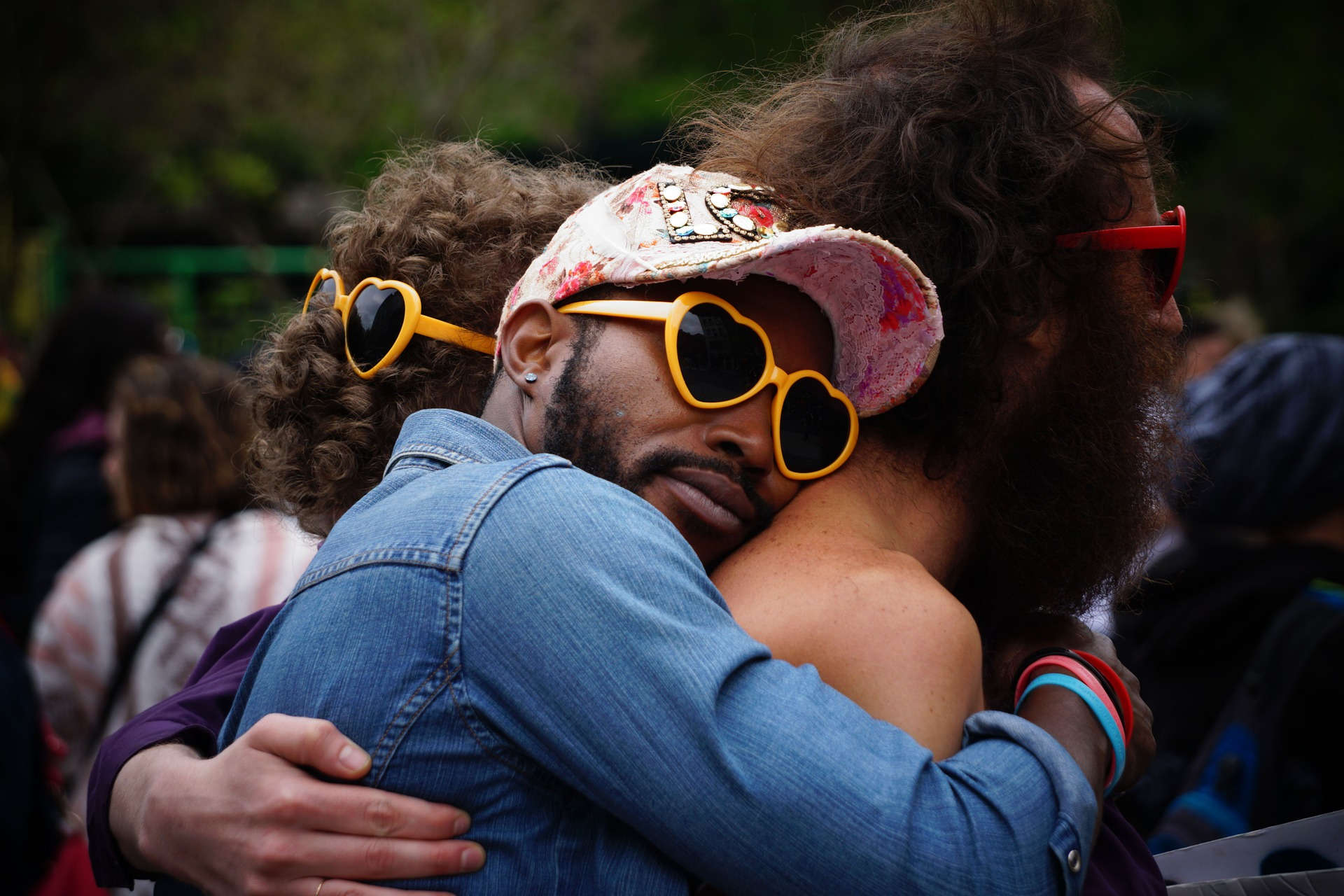 A Black man in sunglasses and a cap is hugging two people from behind at an outdoor event; one is a shirtless man also in sunglasses, and the other is a woman with curly hair.
