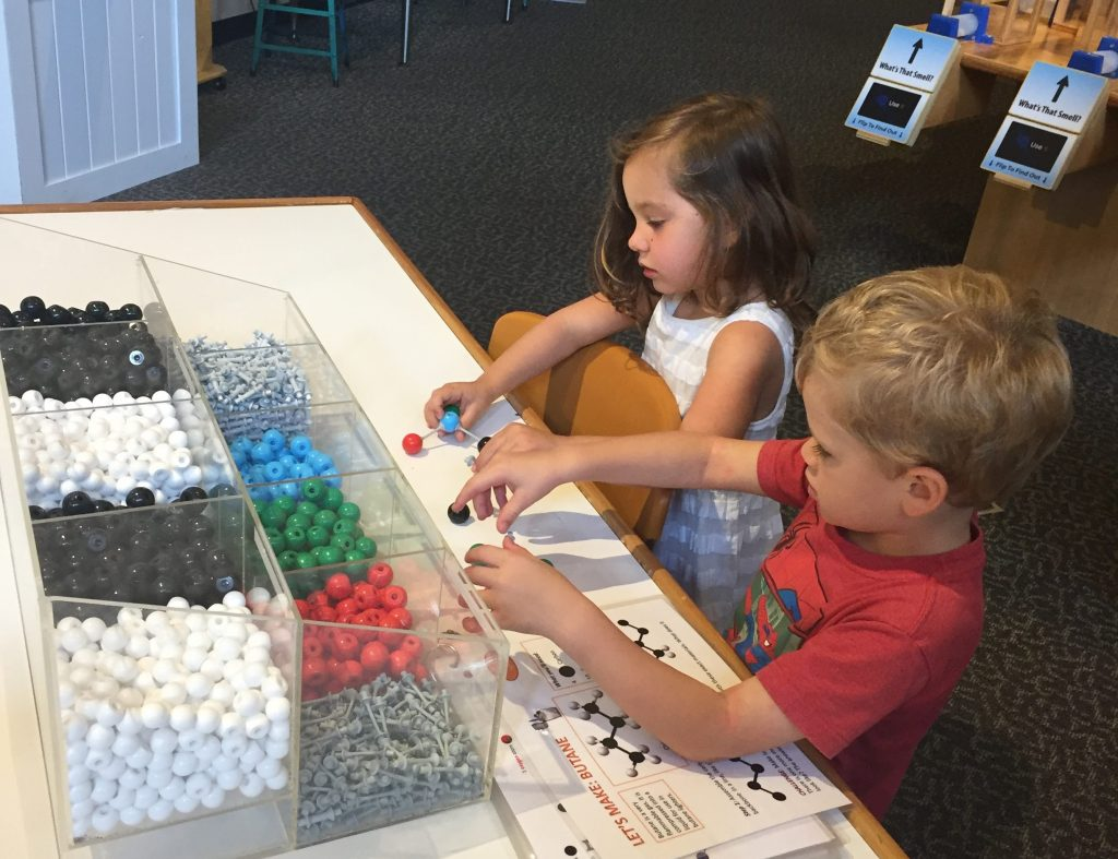 children sitting at a table playing with molecular models