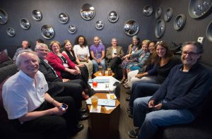 Twelve members of the council enjoying drinks at the end of the conference in an informal room.