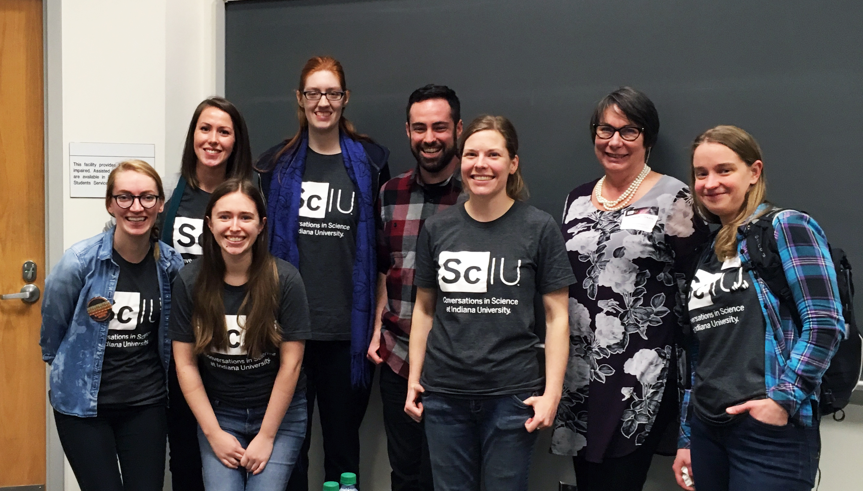 The group of ScIU bloggers and guest speaker standing in front of a chalkboard