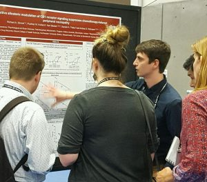 Richard Slivicki is surrounded by four on-lookers while he points at a graph on his poster at the Society for Neuroscience conference in 2016.