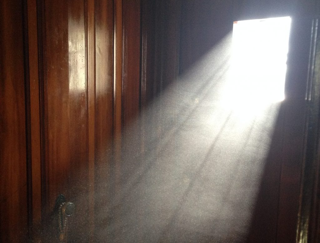 An image of a light beam from window that illuminates the dust in the air, forming a clear white beam in a darkened room.