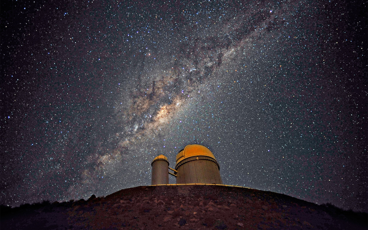 Starry sky above a dome of an observatory. A bright clouds of stars and dust stretches across the sky on a diagonal.
