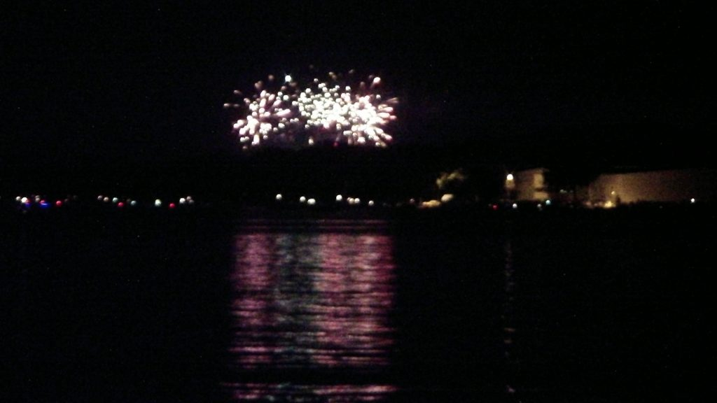A blurred image of fireworks exploding at night over a lake.