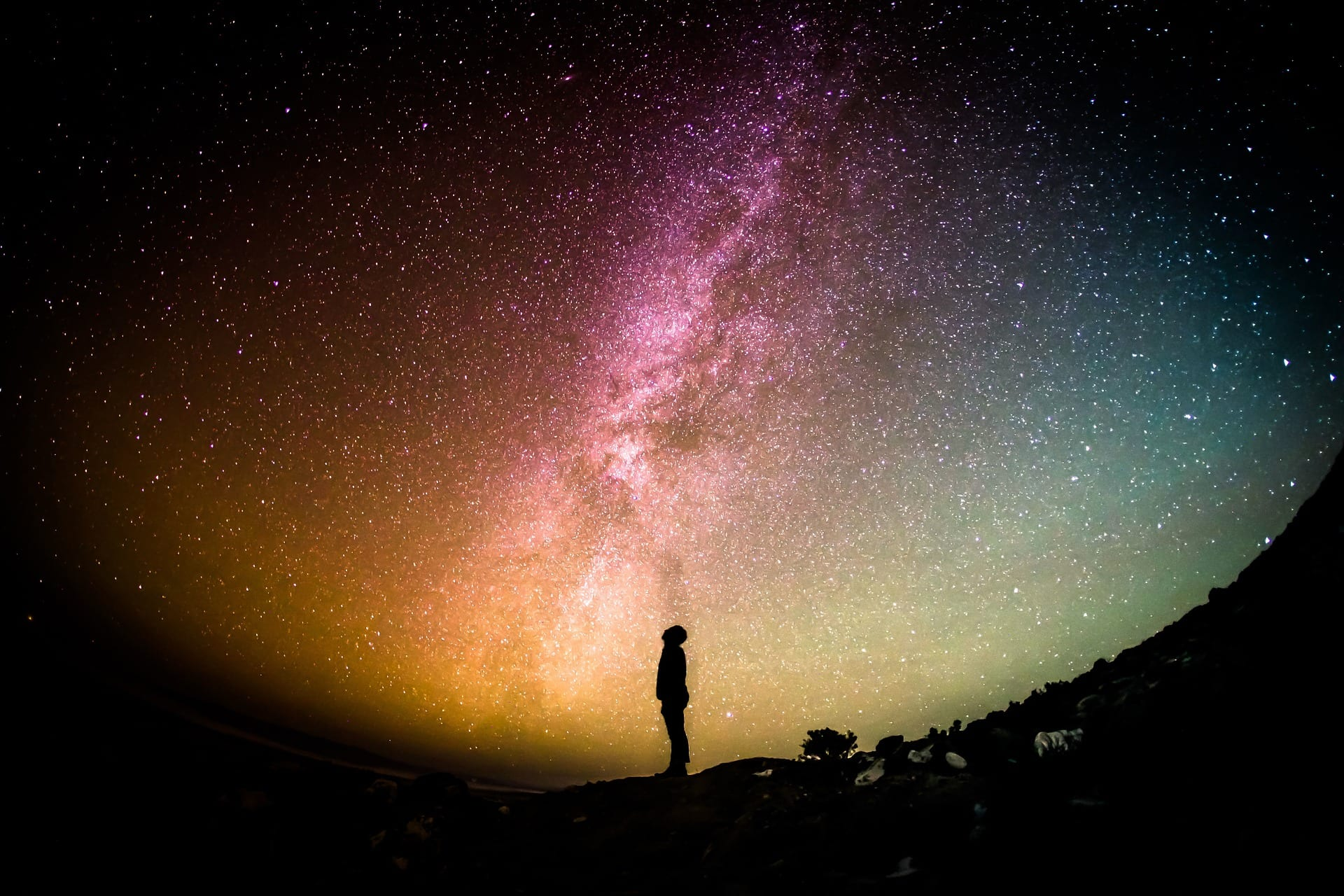 A man stands and looks up into a very starry sky.