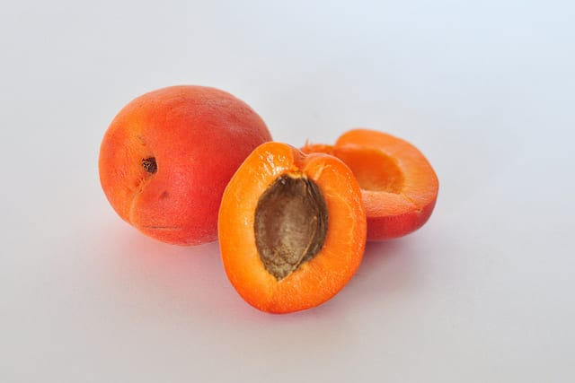 Image of two orange apricots with one apricot split in half to expose the pit in the foreground.