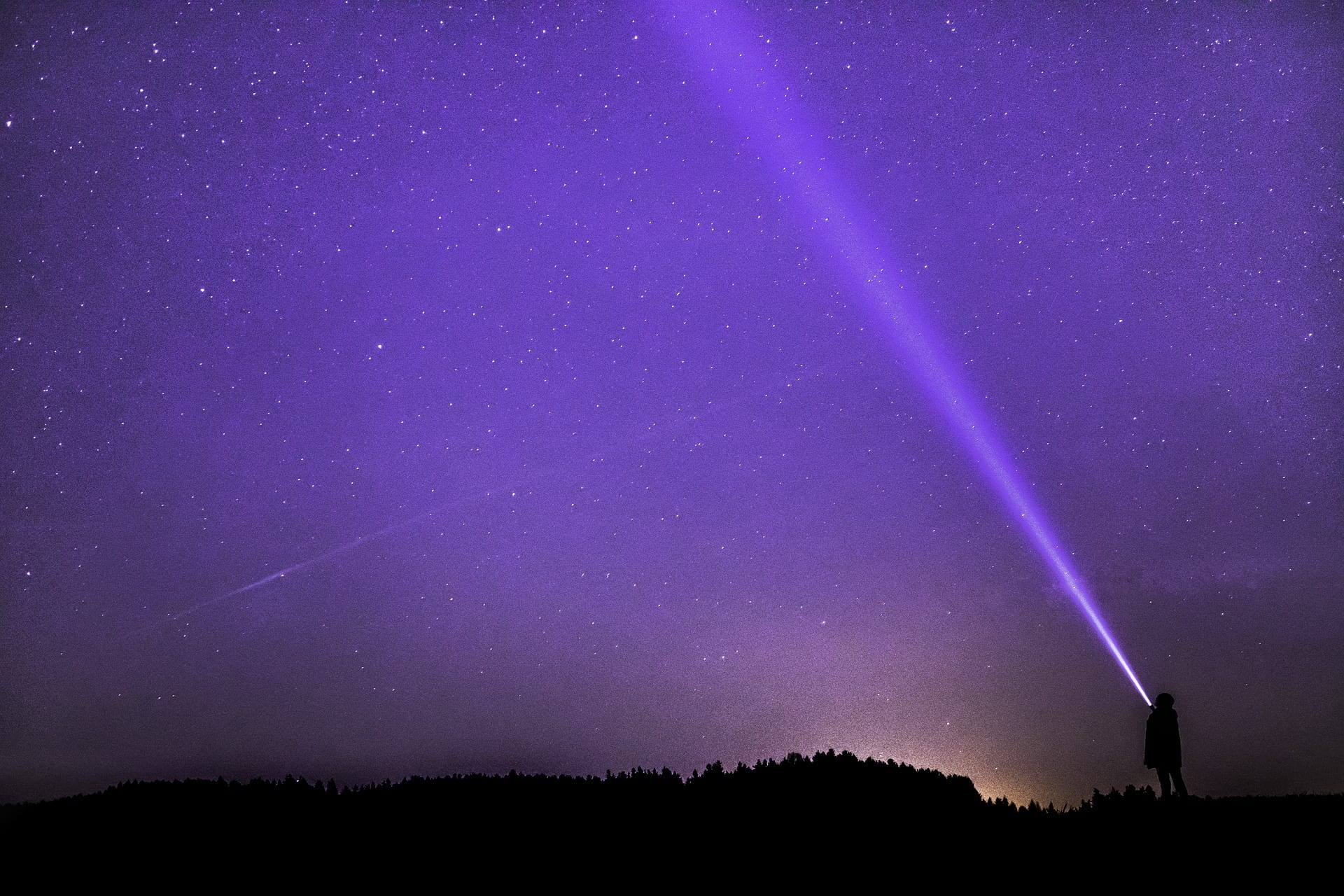 A person shines a flashlight into the night sky, which is filled with stars