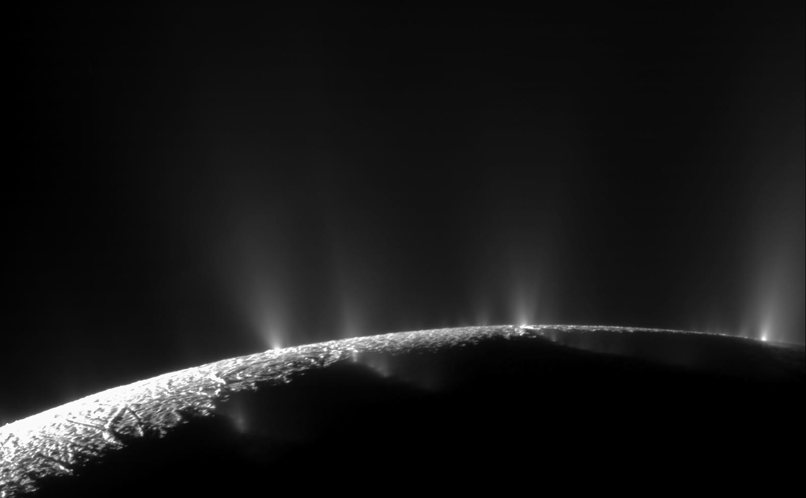 A small section of a darkly lit moon with bright jets of water shooting out from the surface against the blackness of space.