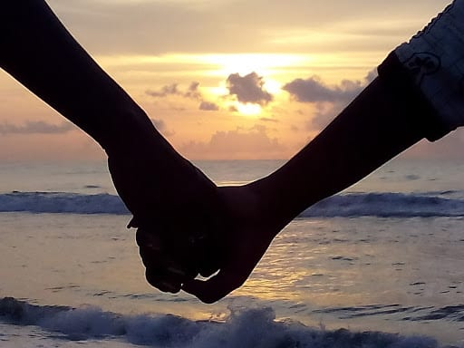 A couple holding hands during a sunset.