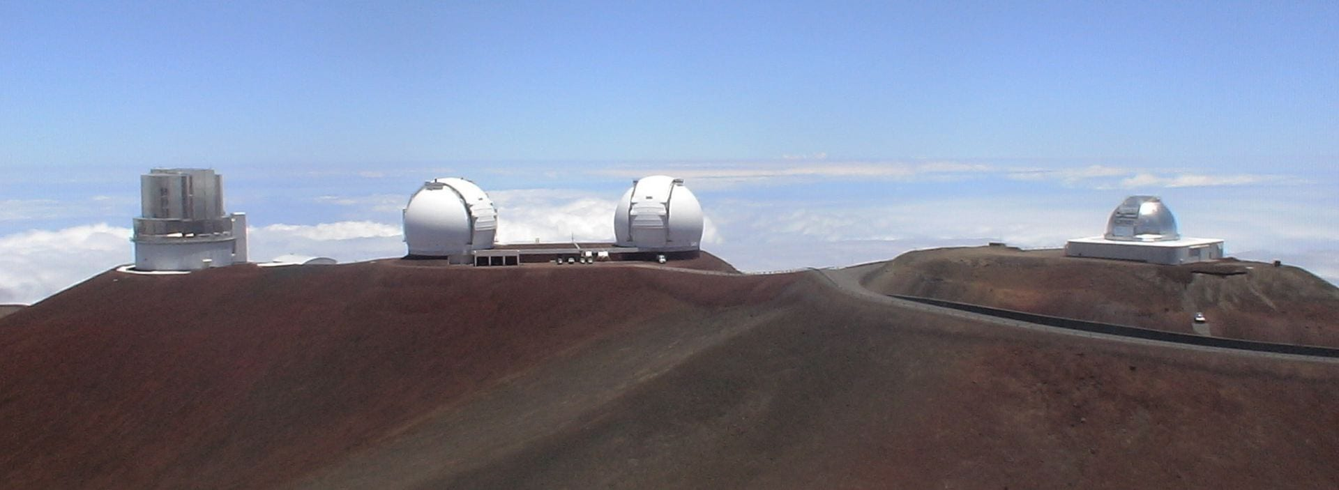 The domes of four telescopes on top of a mountain with the clouds visible below them.