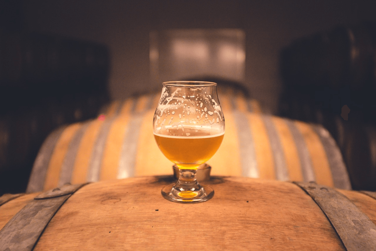 A beer glass sits on a barrel.