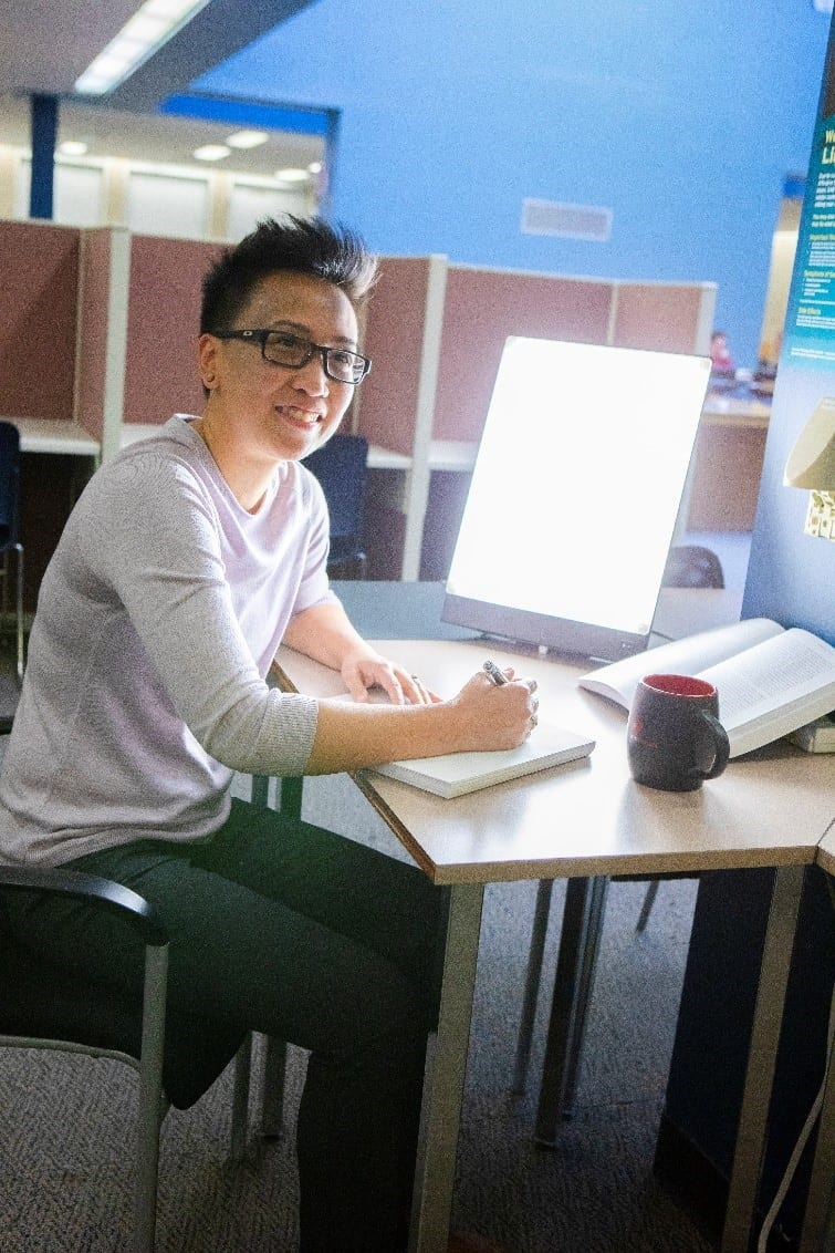 A young man is sitting at a wooden desk at a library, and a textbook, notebook, cup of coffee, and a glowing rectangular screen are sitting on top of the desk. He is holding a pen in his hand, looking up from his notebook, and smiling at the camera. Other cubicles and workstations are visible in the background of the image.
