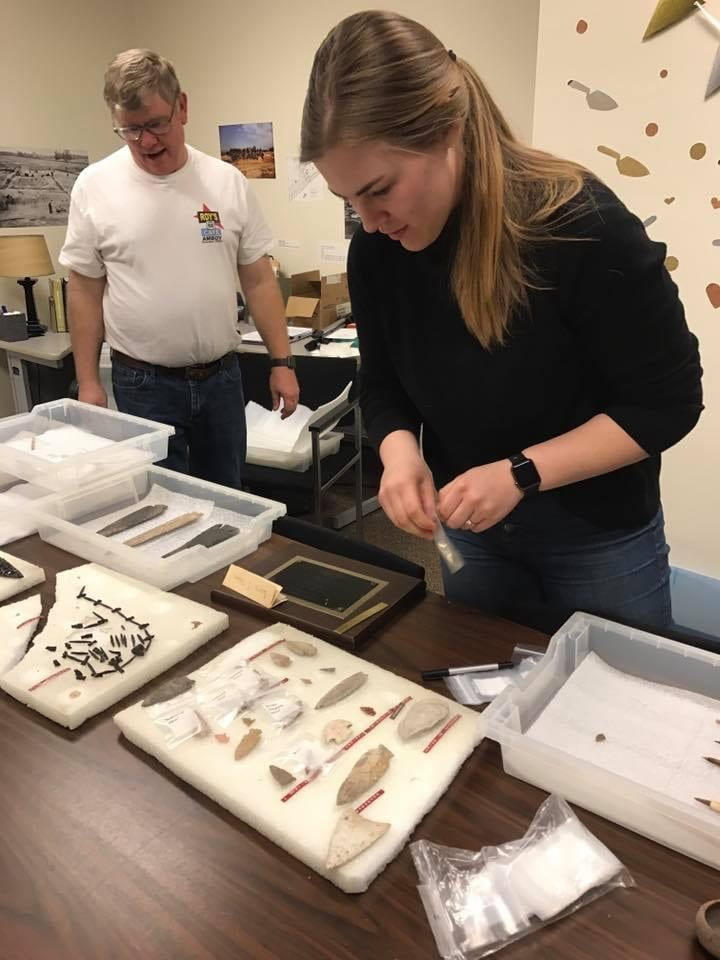 Color photo of archaeologist Molly Mesner identifying and rehousing an archaeological collection at the Glenn A. Black Laboratory of Archaeology.
