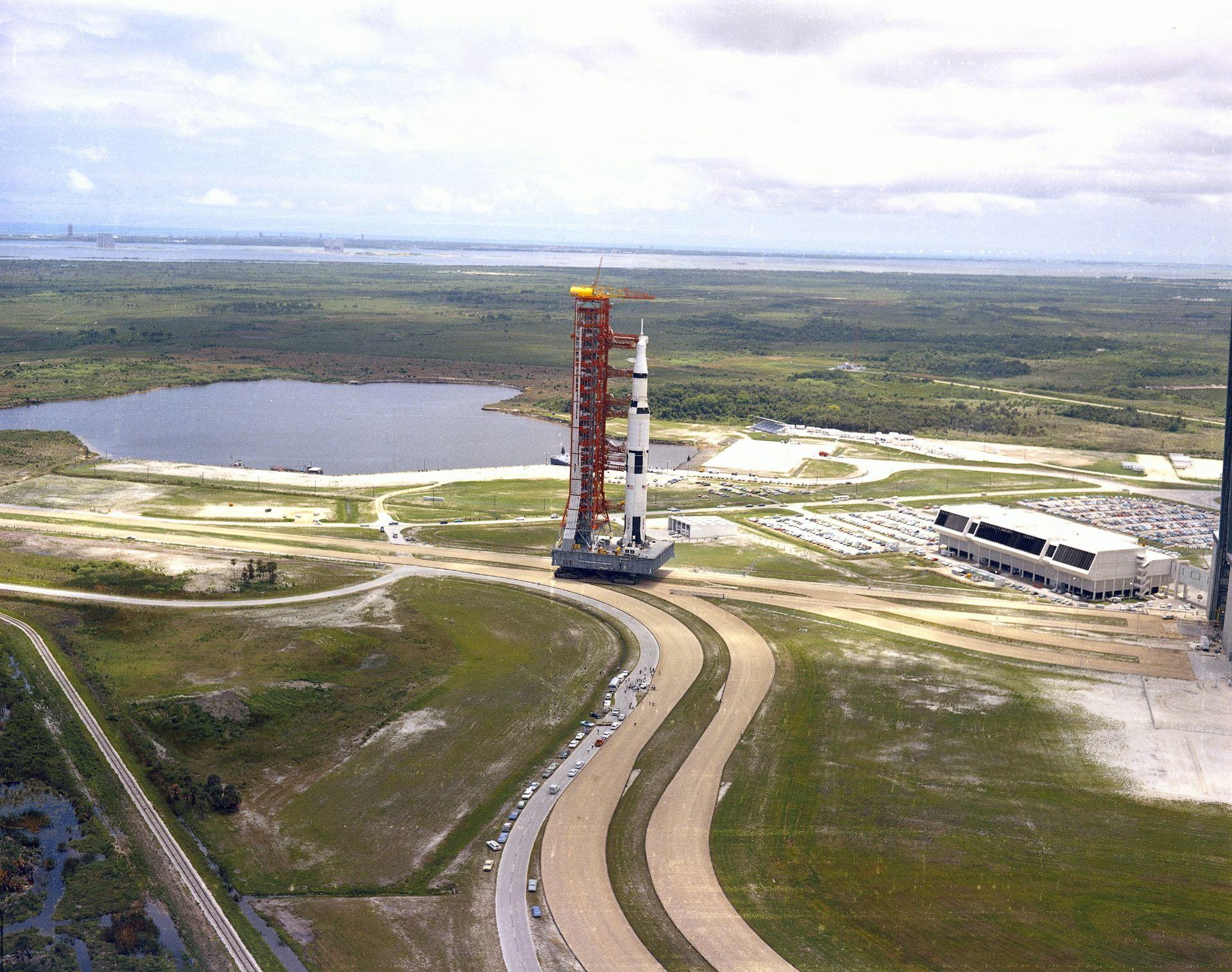 Large rocket on a platform rolling along a road, taking up multiple lanes.