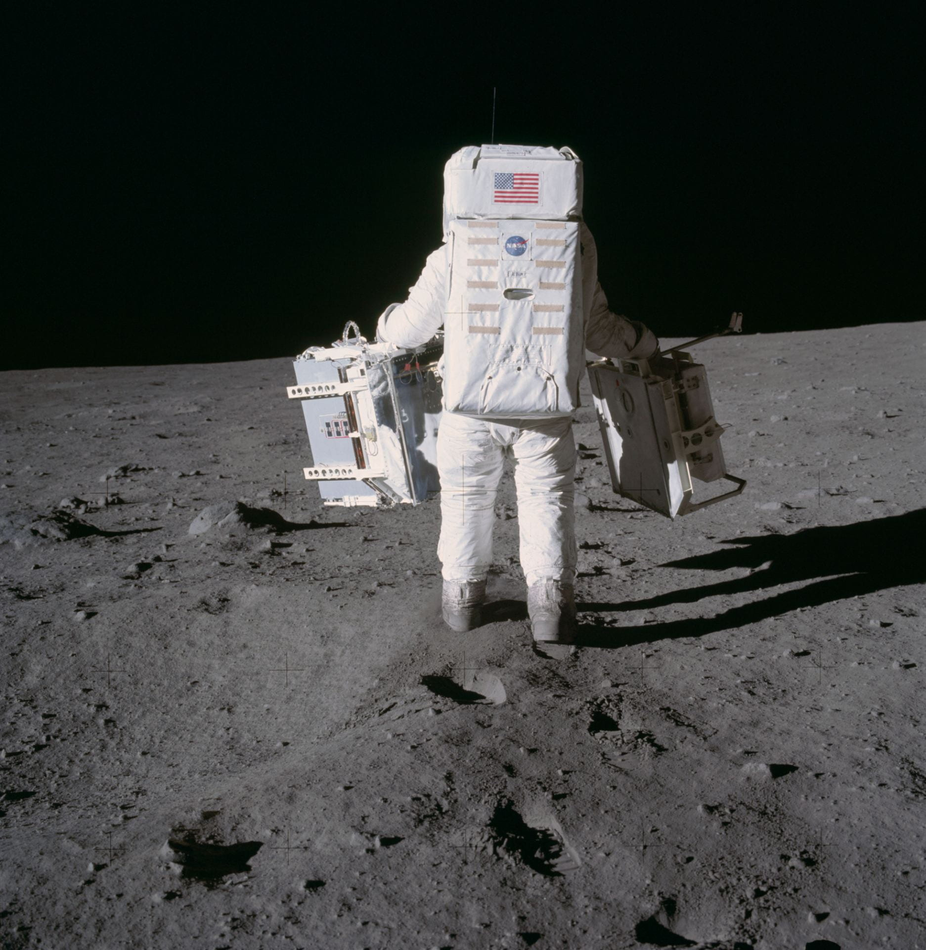The back of an astronaut in a big white space suit on the surface of the moon with the dark void of space in front of him.