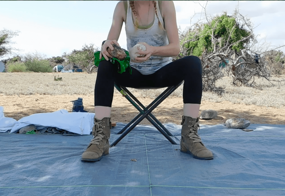 A left-hander sits facing the camera holding a core in her right hand and a hammerstone in her left hand. She is preparing a core to begin making flakes off the rock. Both the core and the flakes produced are considered stone tools.