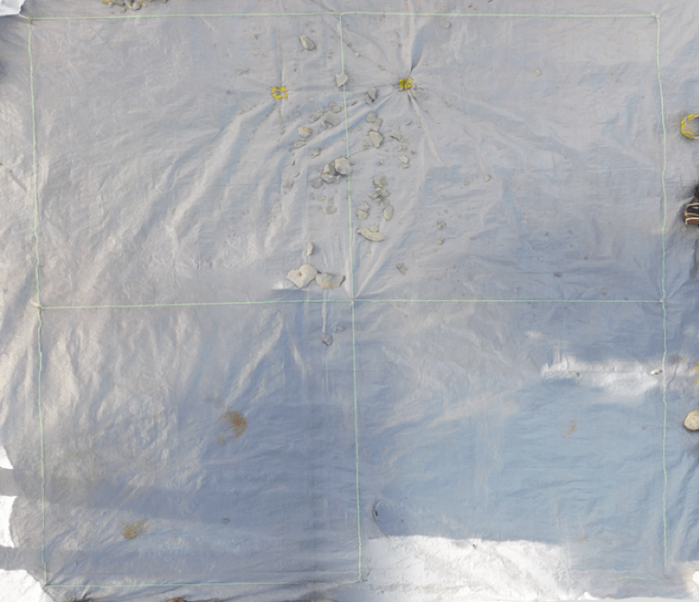 An aerial view of the experimental stone tool making site after a subject has created flakes. The entire 2x2 meter grid is visible and the flakes are scattered in the upper two quadrants close to where the subject was sitting.