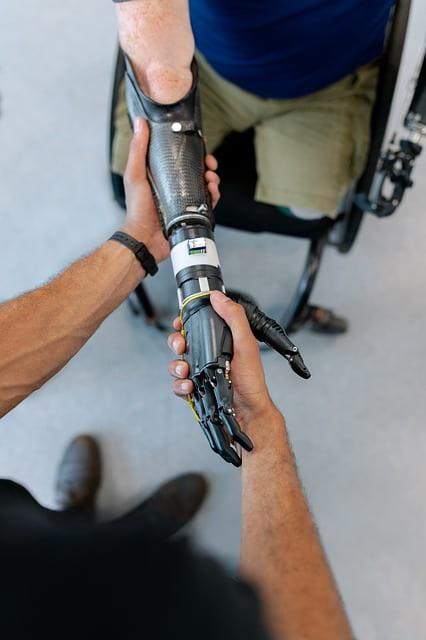 [A man grasps a metal prosthetic arm.]