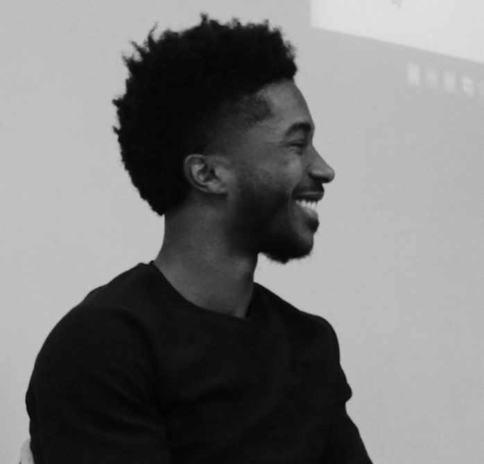[DJ Purnell is captured from the side, smiling. He is sitting at a panel on advice for applying to graduate school]