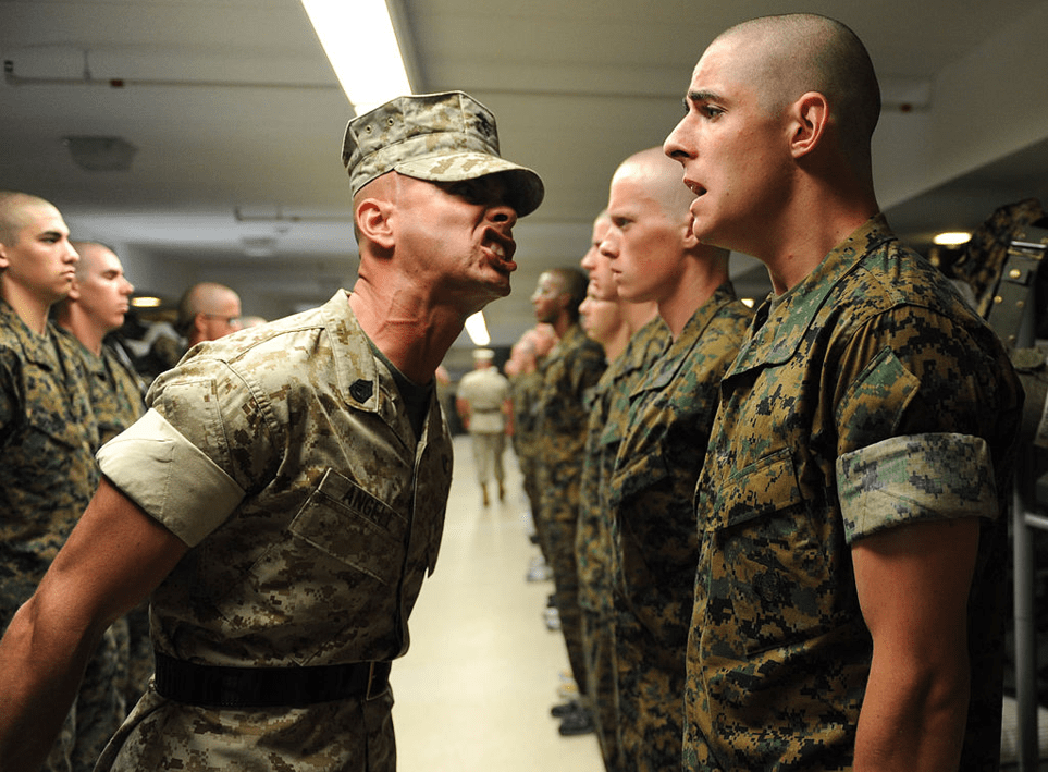 A U.S. Marine Corps drill sergeant yells at a lower-ranked Marine in front of others.